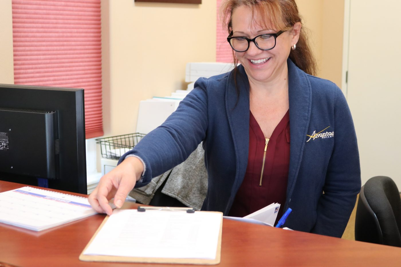 Advantage Rehabs Front Office Manager assisting patients with their intake paperwork in our Cody Clinic