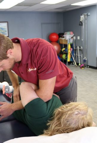 Advantage Rehab therapist in Powell Wyoming using body weight and manual therapy to manipulate the patients spine and release tention in the back and hip